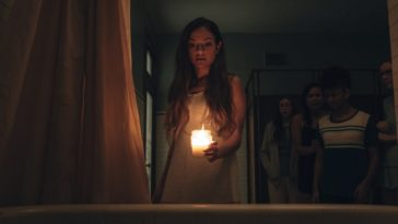 Alice is performing a ritual to summon the school's ghost while holding a candle.