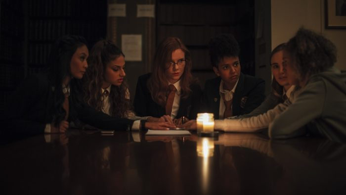 The girls sit around a table during detention trying to perform a seance.