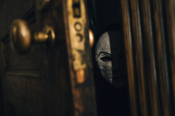 The masked killer peers into a room from the crack of a closet door.