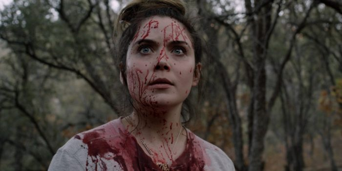 a woman covered in blood stares off screen