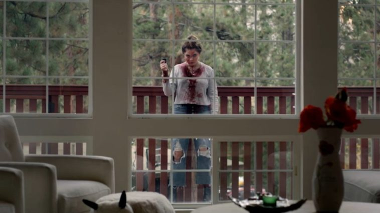 Rebecca stands bloody in the window