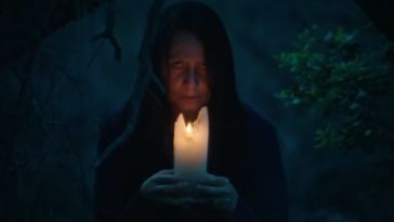 The Boogeywoman holds a candle up to her face