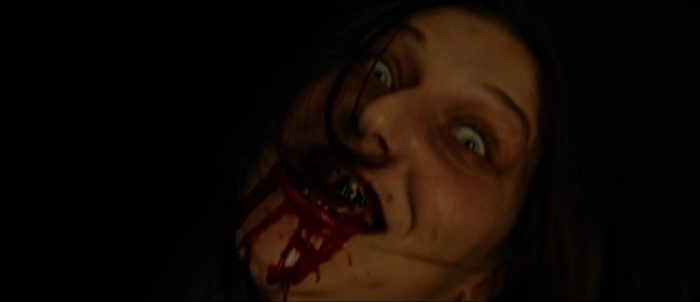 Melissa's face is wide-eyed as blood flows from her mouth in Two Witches