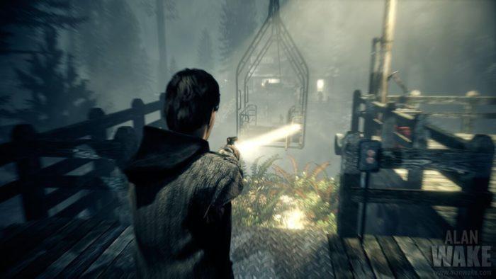 Alan Wake aims his gun and flashlight at a hanging platform