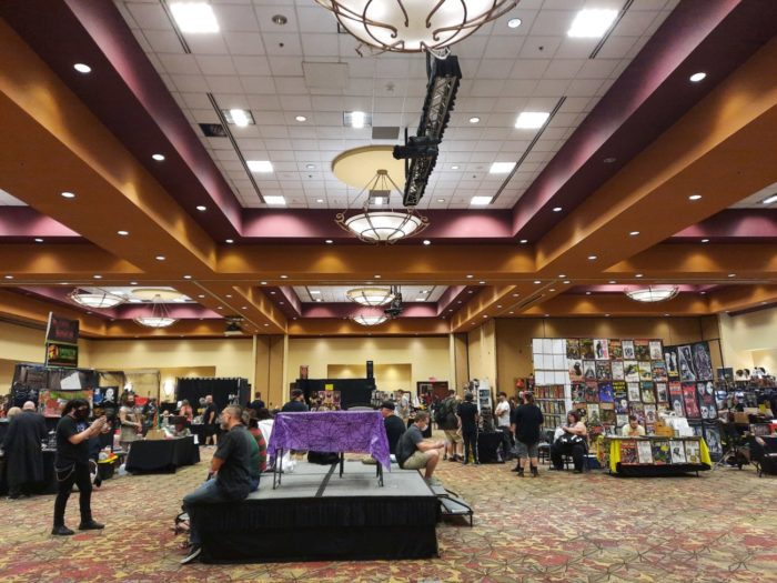 A hotel ballroom with socially distanced booths and attendees