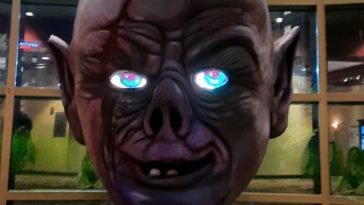 The Mad Monster mascot- a ghoul with glowing blue eyes in front of the Mad Monster Expo banner.