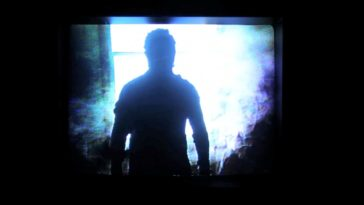A man cast in shadow stands before a window, bathed in intense blue light