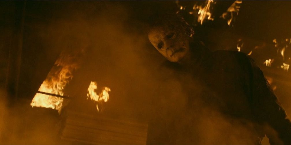 Michael stands in the burning house, staring down at a first responder he just murdered.
