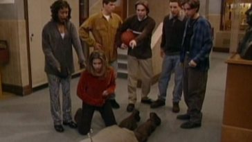 Thr group stand around as Mr Feeny is dead on the ground with a knife lodged into his back.