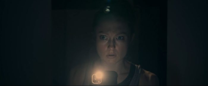 Charlie light's a dark corridor with her cell phone flashlight in Alone With You