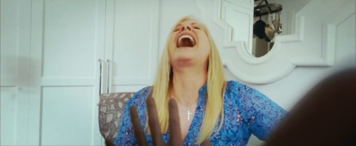 Barbara Crampton throws her head back and cackles while Emily Bennett's character Charlie seeks help from her in Alone With You
