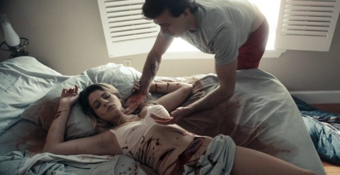 Elway checks castmate Ashley's pulse finding her in a pool of blood from cuts on her abdomen in Death Cast