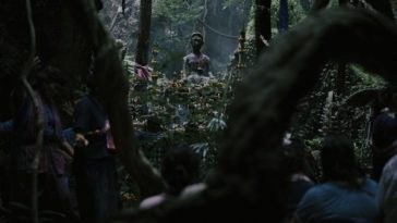A statue of Ba Yan, a Thai deity, sits in the woods surrounded by offerings of flowers and food