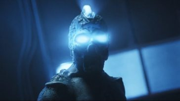The creature from Parallel Minds stares into the camera with eyes and amohawk of ultra bright blue light