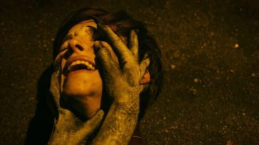 Jane lies on the ground as greyed hands hold her throat and feel her face in Take Back The Night