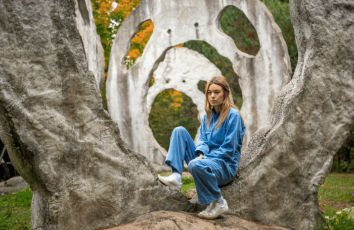 Aurora sits against a rock formation in her blue jumpsuit