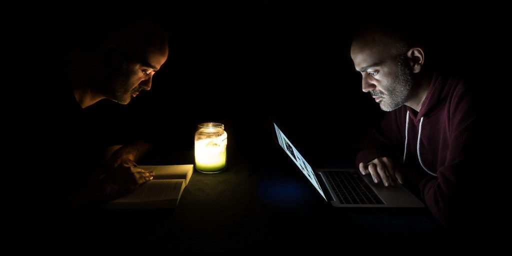 a man reading a print book and a computer by candlelight