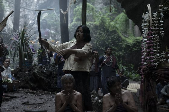 Nim brandishes a sword as she performs a religious ceremony in the woods