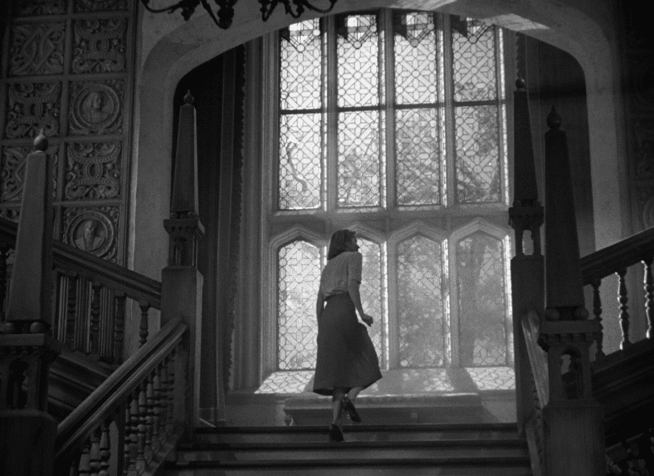 Screenshot of Rebecca shows a woman ascending a grand staircase near a large ornate window