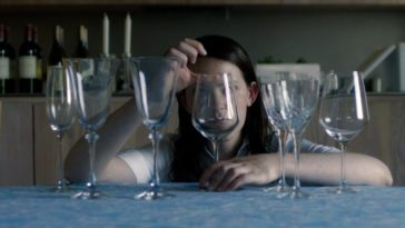 A woman behind a row of fancy glasses